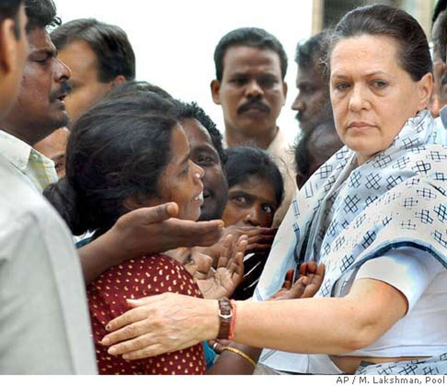 Congress Party President Sonia Gandhi (R) comforts parents of children who were killed in a fire in a school building, during her visit to a hospital in Kumbakonam July 18, 2004. Around 90 children were burnt to death when a fire swept through a private school in Tamil Nadu's Thanjavur district on Friday. REUTERS/M. Lakshman/Pool 0 Photo: POOL