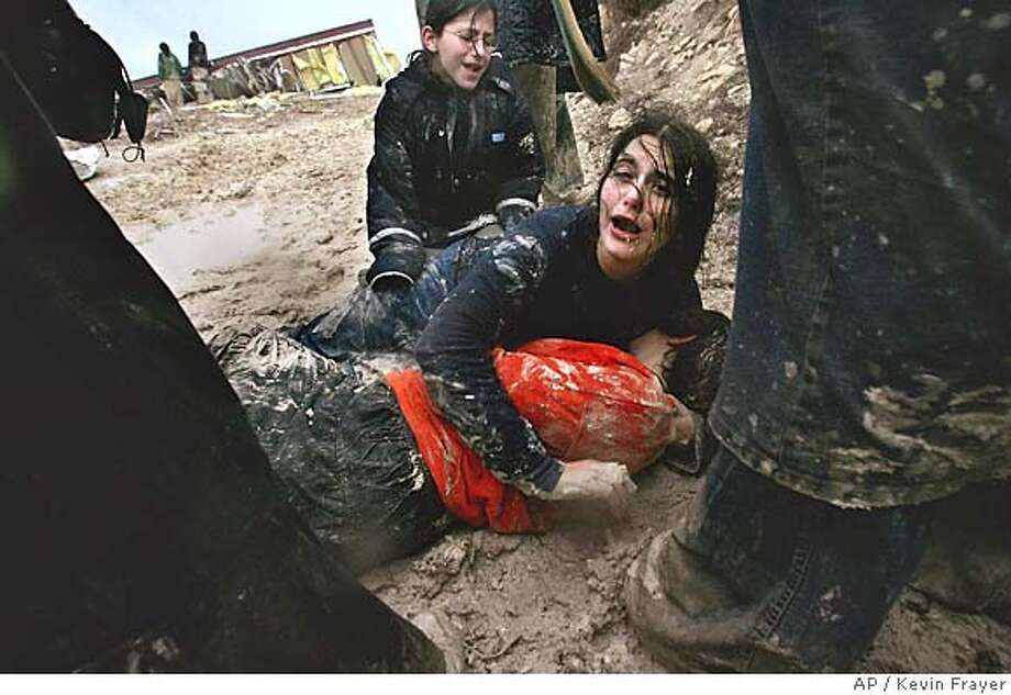 Israeli settler girls cry in the mud after being dragged away by Israeli army soldiers dismantling an illegal structure at an outpost outside the Jewish settlement of Yitzhar, near the West Bank town of Nablus, Monday, Jan 3, 2005. Some 100 settlers who came from other settlements confronted police and army trying to evacuate two caravans from the illegal outpost while Jewish settler leaders warned that hundreds, and possibly thousands, of soldiers could refuse to carry out orders to evict Gaza Strip settlers, a sign of the difficulties the army could face in carrying out the Gaza withdrawal planned by Prime Minister Sharon. (AP Photo/Kevin Frayer) Photo: KEVIN FRAYER
