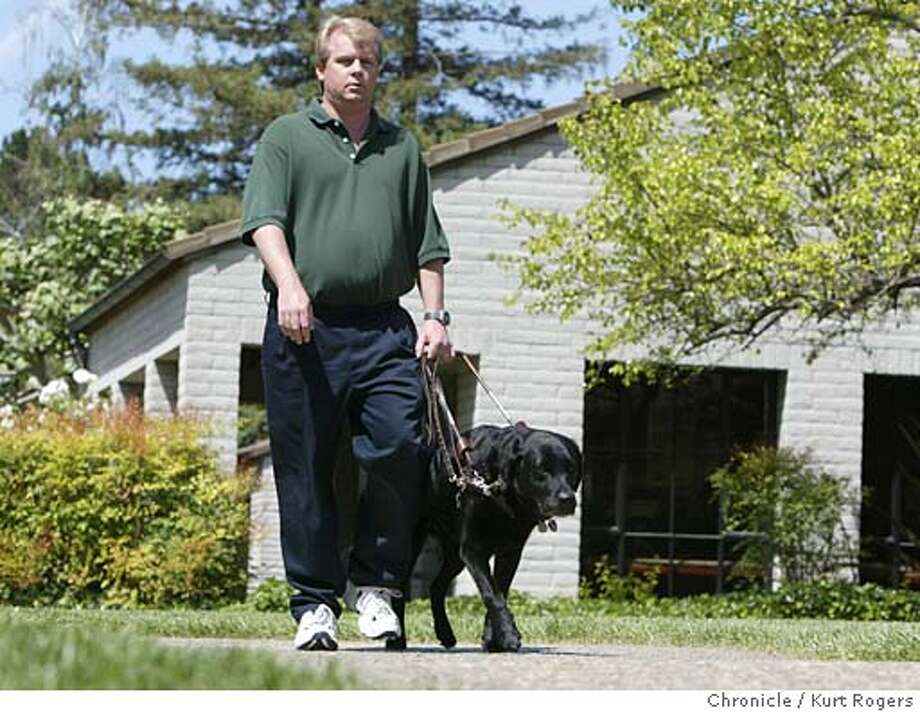 Ken Altenburger who has worked for the guide dogs for the blind for seven years walks Honcho through the Guide Dogs For the Blind's campus in San Rafael.  Five years ago, the Chronicle first reported that Guide Dogs For the Blind was sitting on a nest egg of close to $200 million -- a stash so large that critics blasted the group for continuing to raise money. And Guide Dog's fundraising was hit hard. But despite the temporary blip of bad publicity, the charity says it recovered and now continues to raise far more money than it spends each year 5/13/04 in San Rafael,CA.  Kurt Rogers/The Chronicle Photo: Kurt Rogers