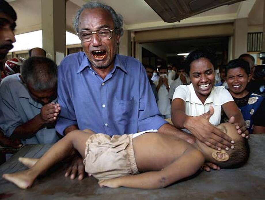 ** ADVANCE FOR MONDAY, JAN. 3 **FILE**A victim's family cries as they receive the body of their son at the Galle Hospital, in Galle, Sri Lanka, Monday, Dec. 27, 2004. Images showing the bodies of Asian earthquake and tidal wave victims were published on many front pages, while such graphic images rarely appeared on television news shows reporting the disaster. (AP Photo / Vincent Thian) HFR 01-03-04. ADVANCE FOR MONDAY, JAN. 3 Photo: VINCENT THIAN