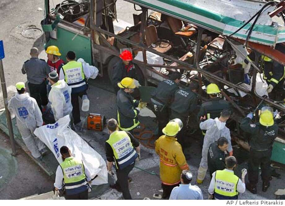 A body is carried from the scene of a suicide bomb attack in downtown Jerusalem Thursday Jan. 29, 2004. A suicide bomber blew up inside a bus killing at least 10 people and wounding about 30. The attack took place near Prime Minister Ariel Sharon's official residence. (AP Photo/Lefteris Pitarakis) Photo: LEFTERIS PITARAKIS