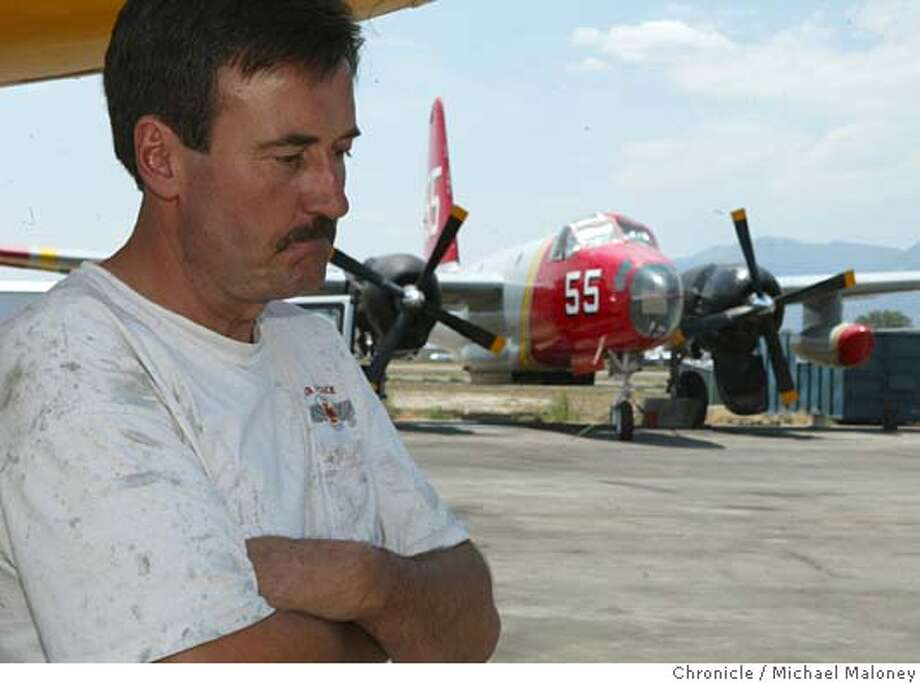 Tim Christy, a pilot for Minden Air Corp. which owns the Lockheed P2 seen in the background is frustrated that he could not help fight the fire. The tanker and another belonging to Minden Air was grounded last May and was waiting to be certified this coming Monday.  Some residents of Carson City, Nevada are questioning why more air tankers were not used to stop the fire west of town. The FAA grounded many of the military surplus tanker planes last May when 5 people died in 2002 in two seperate incidents caused by metal fatigue cracks.  A fire near Carson City, Nevada has burned over 7,000 acres including 14 homes. It is 50% contained as of this morning.  Photo by Michael Maloney / San Francisco Chronicle Photo: Michael Maloney