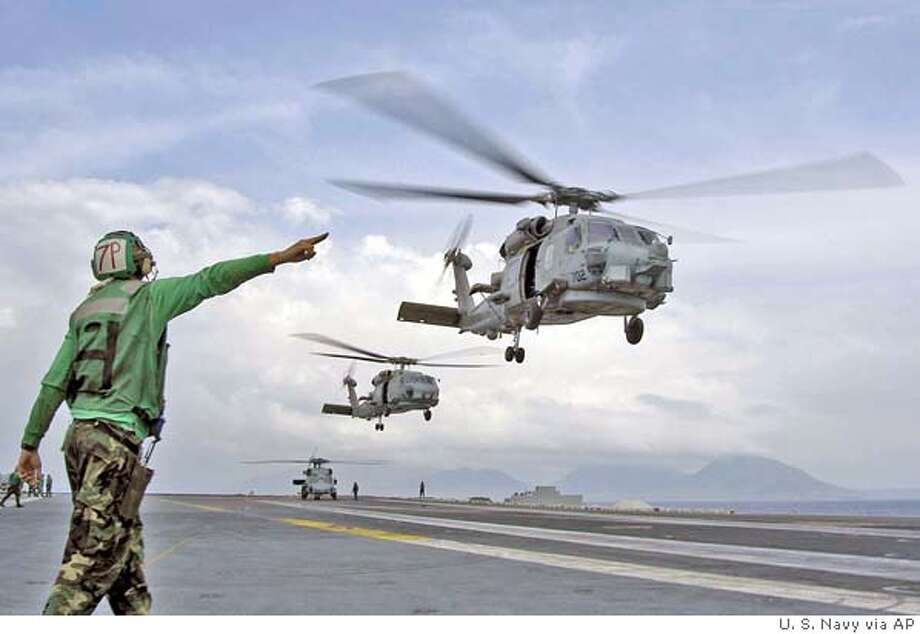 This image released by the US Navy Sunday Jan. 2, 2005 helicopters depart from the USS Abraham Lincoln (CVN 72) enroute to Aceh, Sumatra, Indonesia. The helicopters are transporting supplies, bringing in disaster relief teams and supporting humanitarian airlifts to tsunami-stricken coastal regions. The Abraham Lincoln Carrier Strike Group is currently operating in the Indian Ocean off the waters of Indonesia and Thailand. (AP Photo/U.S. Navy photo)