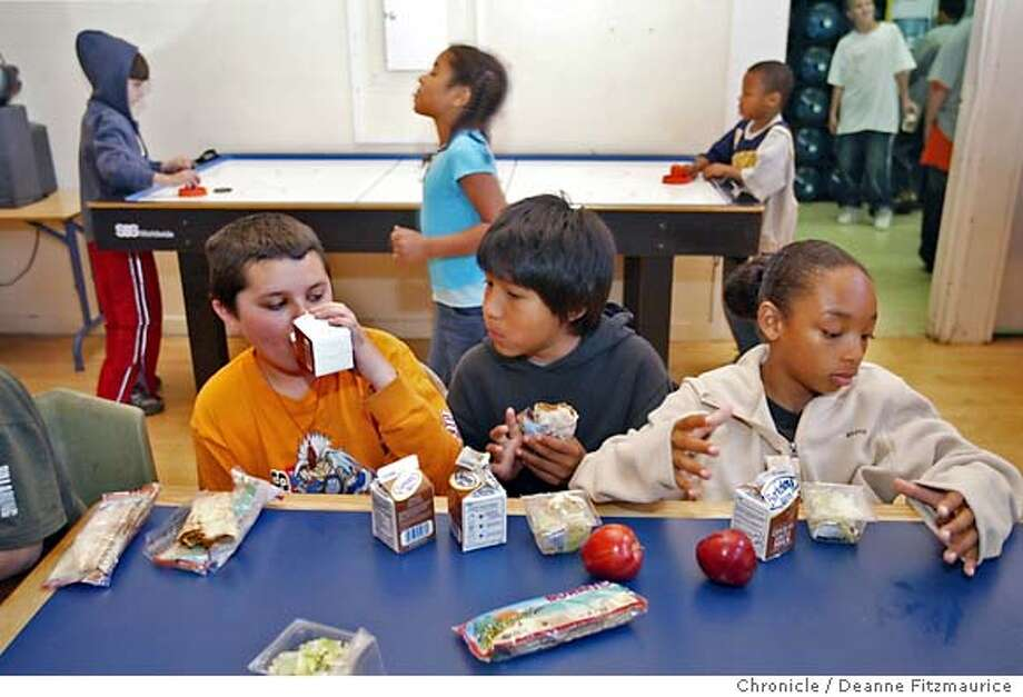 (l to r) Elliot Ward, Lemoine Garcia, and Dejon Cassanova eat the lunch provided. Walking behind them is Eysia Miranda. Lunch is served at the Mission Boys and Girls Club as part of the summer lunch program for low-income kids. This was shot in San Francisco.  Deanne Fitzmaurice / The Chronicle Photo: Deanne Fitzmaurice
