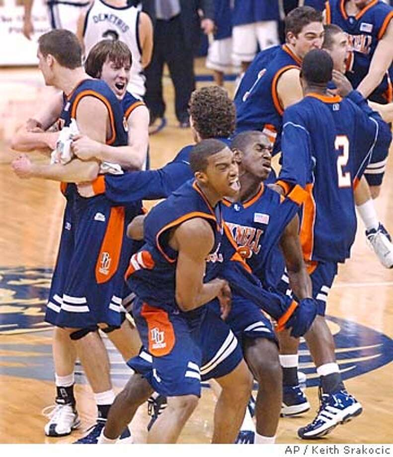 Bucknell's basketball team celebrates as time runs out in their 69-66 upset win over Pittsburgh in Pittsburgh on Sunday, Jan. 2, 2005 Bucknell's leading scorer, Chris McNaughten , upper left, is hugged by teammate John Clark as teammates Charles Lee, left center, and Holland Mack hug at center.(AP Photo/Keith Srakocic) Photo: KEITH SRAKOCIC