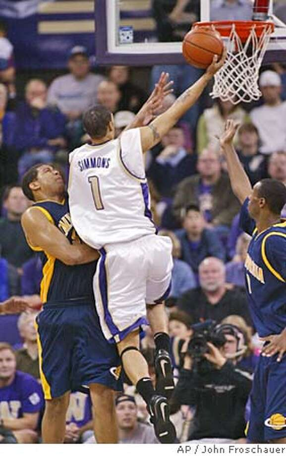 Washington's Tre Simmons drives to the basket against California's David Paris, left, and Rod Benson, right, during the second half of the Pac-10 opening game in Seattle Friday, Dec. 31, 2004. Washington won 81-67 with Simmons leading the scoring for Washington with 18 points. (AP Photo/John Froschauer) Photo: JOHN FROSCHAUER