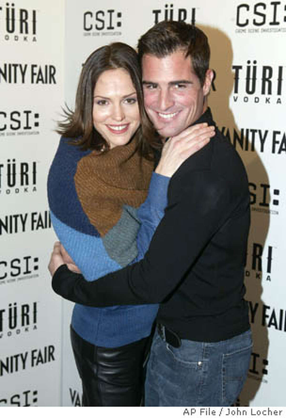 ** FILE **CSI: Crime Scene Investigation cast members Jorja Fox, left, and George Eads embrace on their way into a Vanity Fair party in Las Vegas, in this Dec. 14, 2003, file photo. Fox and Eads, who play investigators Sara Sidle and Nick Stokes, were fired after asking for more money to stay on the show, according to the reports. (AP Photo/John Locher/FILE)