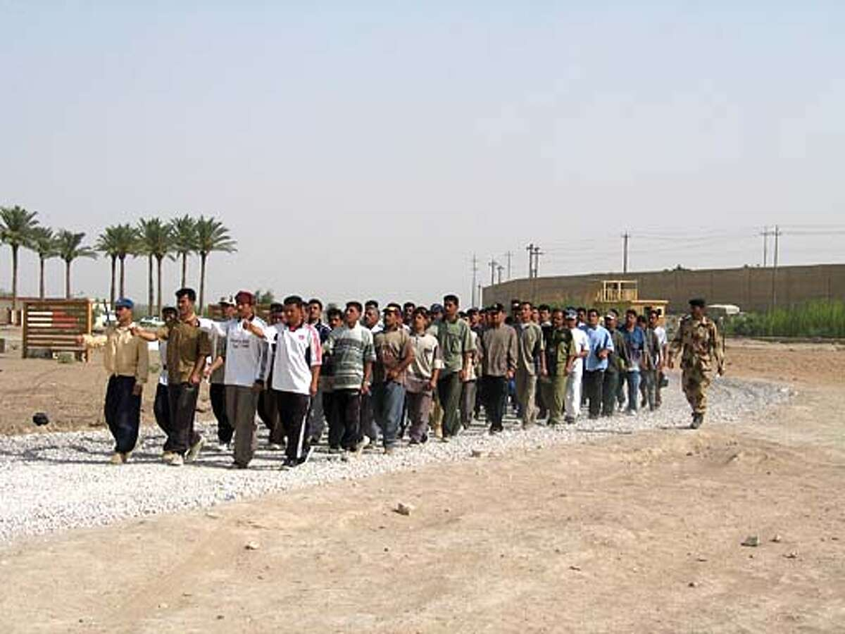 A group of about Iraqi 50 men practice marching in formation in civilian clothes in Ramadi. Chronicle photo by John Koopman