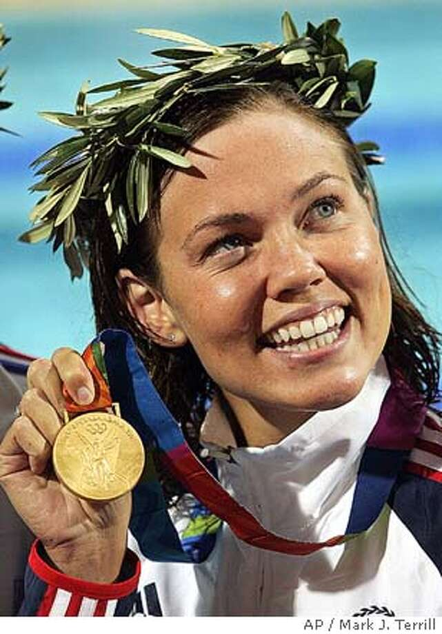 Gold medalist Natalie Coughlin of the U.S. shows her medal after winning the 100m backstroke the 2004 Olympic Games Monday, August 16 2004 in Athens, Greece. (AP Photo/Mark J. Terrill) Ran on: 08-17-2004  Natalie Coughlin puts her gold-medal smile on display. Photo: MARK J. TERRILL