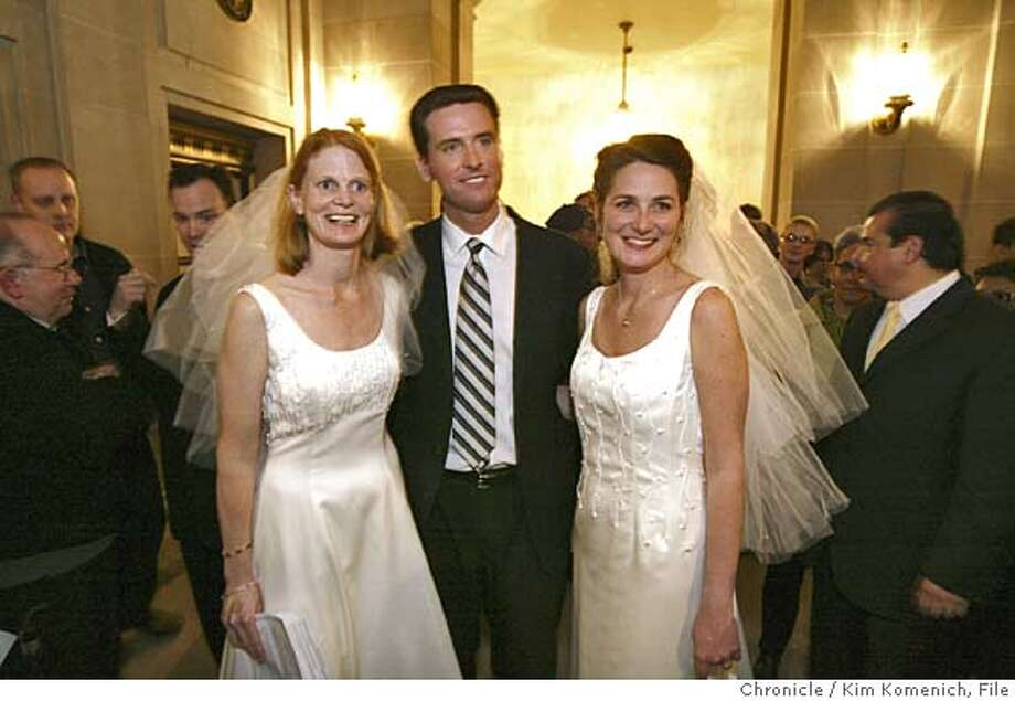 ** FILE ** San Francisco Mayor Gavin Newsom stands between newlyweds Cissie Bonini, left, and Lora Pertle, during a reception at San Francisco City Hall in this Friday, Feb. 13, 2004, file photo. To hear Mayor Gavin Newsom tell it, his decision to order the city to grant marriage licenses to same-sex couples was purely an act of principle. But, as other cities and jurisdictions move to follow his lead, the 36-year old Newsom has cemented his stature as one of the nation's best-known mayors and one ofthe Democratic Party's brightest lights. Hundreds of same sex couples crowd S.F. City Hall to get married after the City passed legislation allowing same sex couples to marry.  Photo by Kim Komenich in San Francisco. Photo: Kim Komenich