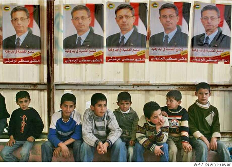 Palestinian boys sit under posters for presidential candidate and human rights activist Mustafa Barghouti outside a meeting where he was speaking in the village of Sa'ar near the West Bank town of Hebron, Thursday, Dec. 30, 2004. Palestinians will go to the polls Jan. 9 in elections to choose a successor to Yasser Arafat. (AP Photo/Kevin Frayer) Photo: KEVIN FRAYER
