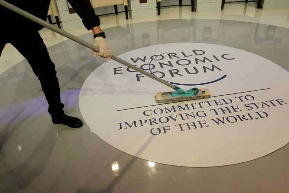 """A woman cleans the floor prior to a session at the World Economic Forum, WEF, in Davos, Switzerland, Wednesday, Jan. 25, 2012. The overarching theme of the meeting, which will take place from Jan. 25 to 29, is """"The Great Transformation: Shaping New Models"""". (AP Photo/Michel Euler) Photo: Michel Euler / AP"""