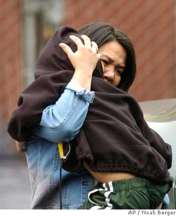 Lydia Ghazzawi, whose brother Angelo dela Cruz is being held hostage by Iraqi insurgents, holds her son as she leaves her Pacifica, Calif., apartment on Monday, July 12, 2004. Insurgents have threatened to behead Cruz, a truck driver working in Iraq, unless Filipino troops pull out of the country. (AP Photo/Noah Berger) Photo: NOAH BERGER