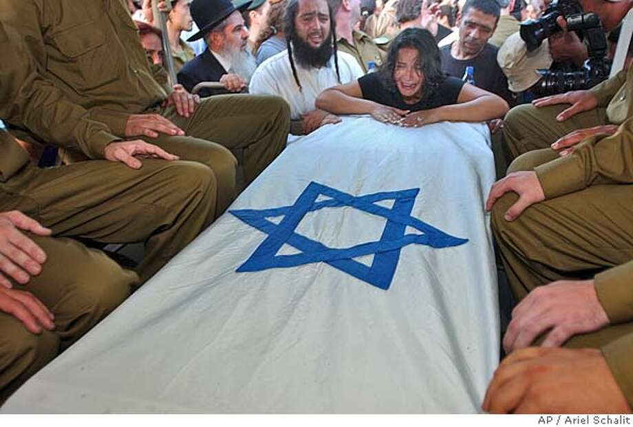 A relative weeps over the flagged coffin of Sergeant Maayan Na'im during her funeral at the military cemetery in Holon south of Tel Aviv, Sunday, July 11, 2004. Na'im, 19, was killed and five people were seriously wounded Sunday when Palestinian militants blew up a bus stop with a nail-studded bomb hidden in roadside shrubs in Tel Aviv. (AP Photo/Ariel Schalit) Ran on: 07-12-2004  At a cemetery outside of Tel Aviv, a relative weeps over the flagged coffin of Israeli soldier Mayan Na'im, killed in a terrorist explosion. Photo: ARIEL SCHALIT