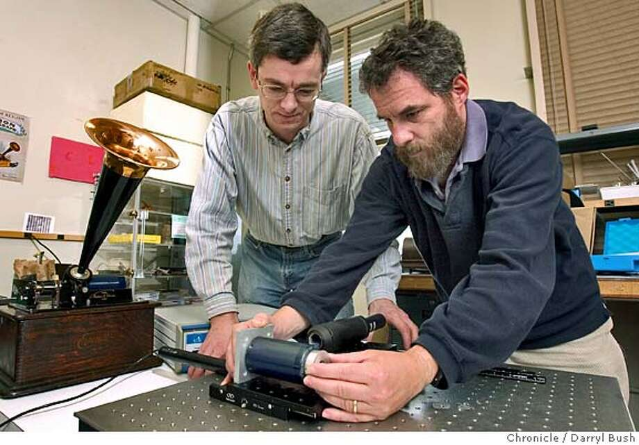 Scientists Vitaliy Fadeyev, left, Carl Haber, right, and at Lawrence Berkeley National Laboratory setup a confocal probe which makes topographical measurements on cylinder recordings made in the 19th century. The old Edison Standard Phonograph is on left. Haber and Fadeyev work on two new ways to recover sound from old recordings on cylinders and disks.  7/9/04 in Berkeley  Darryl Bush / The Chronicle Photo: Darryl Bush