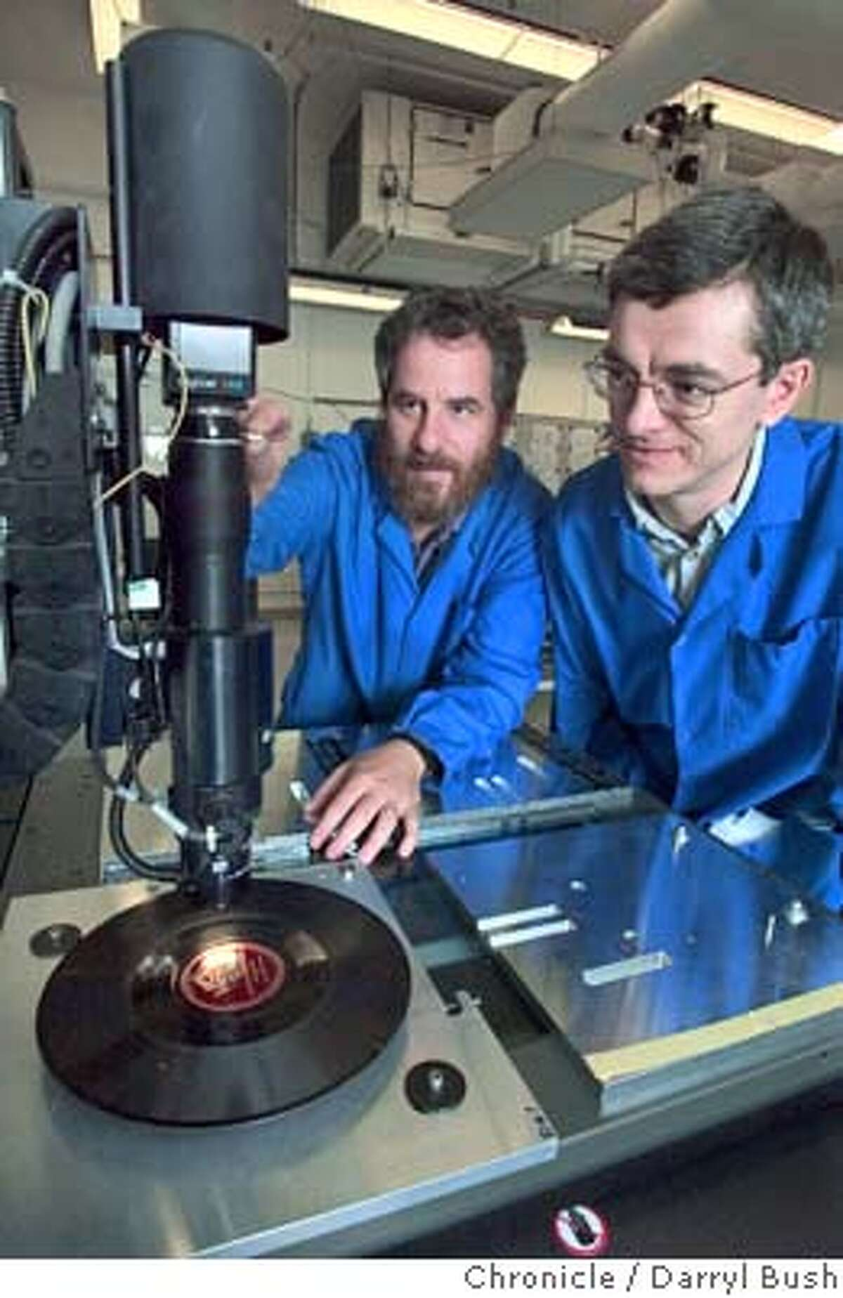 Scientists Carl Haber, left, and Vitaliy Fadeyev, right, make adjustments on setting up an early 78rpm shellac disk pressed in 1932 of an early Enrico Caruso recording, underneath the Smartscope digital microscope, inside a clean room at Lawrence Berkeley National Laboratory where they work on two new ways to recover sound from old recordings on cylinders and disks. 7/9/04 in Berkeley Darryl Bush / The Chronicle