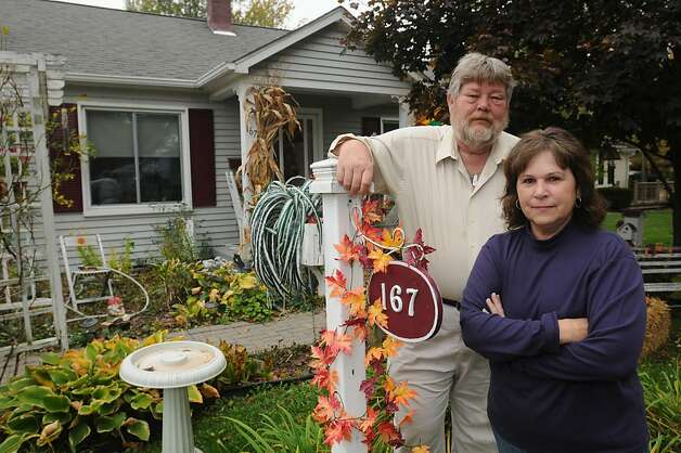 In this Wednesday, Oct. 12, 2011, photo, Dan and Maggie Micoff stand in front of their house in Marine City, Mich. The Micoffs bought their two-bedroom home in the Detroit suburb in 2003. They paid $119,000. Eight years later, they're underwater with a 6 percent loan.  Today's record-low mortgage rates are out of reach for millions of U.S. homeowners who would benefit from them most, but the Obama administration is hoping at least 1 million of these borrowers will take advantage of its refinancing program under the more lenient rules unveiled Monday, Oct. 24, 2011.  (AP Photo/The Port Huron Times Herald, Mark R. Rummel) Photo: Mark R. Rummel, Associated Press