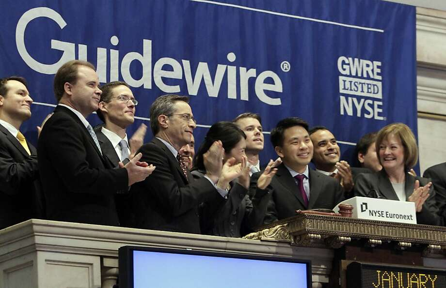 Marcus Ryu, third from right, president and CEO of Guidewire Software, is applauded as he rings the opening bell  of the New York Stock Exchange, before his company begins trading, Wednesday, Jan. 25, 2012. Guidewire is the first technology IPO to list on the NYSE in 2012. (AP Photo/Richard Drew) Photo: Richard Drew, Associated Press