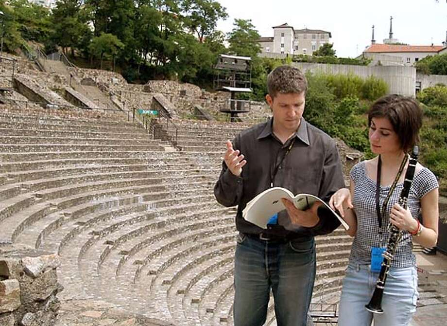 Jeannie Psomas gets some advice about her clarinet solos from Music Director Edwin Outwater before their concert in a Roman Amphitheatre (Grand Theatre) in Lyon, France. HANDOUT