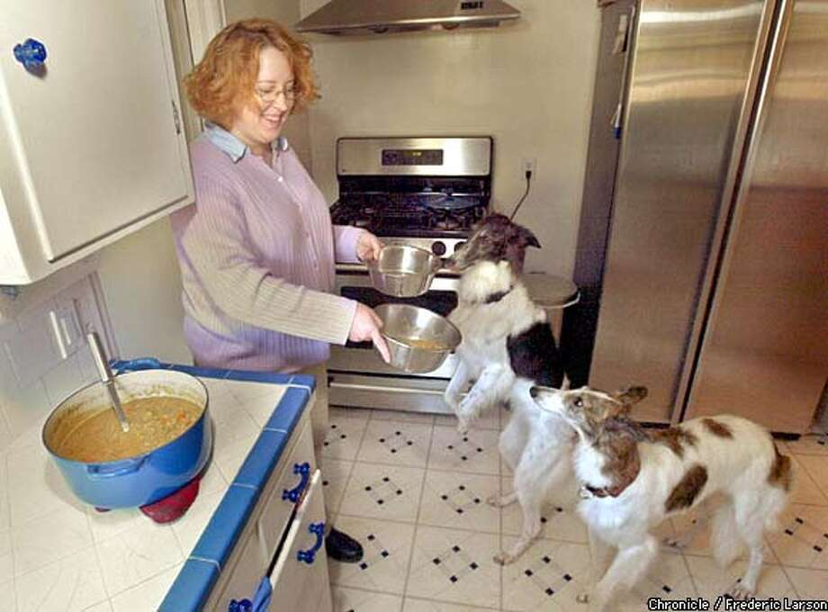 Emily Olson feeds her Silken Windhounds, Daisy, left, and Abby, homemade Doggie Turkey Stew. Chronicle photo by Frederic Larson