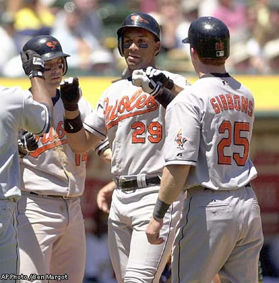 Baltimore Orioles' Chris Singleton (29) is welcomed at home plate by teammates Melvin Mora (6), Mike Bordick (14) and Jay Gibbons (25) after hitting a three run homer in the first inning agains tht Oakland Athletics Thursday, May 23, 2002, in Oakland, Calif. AP Photo / Ben Margot Photo: BEN MARGOT