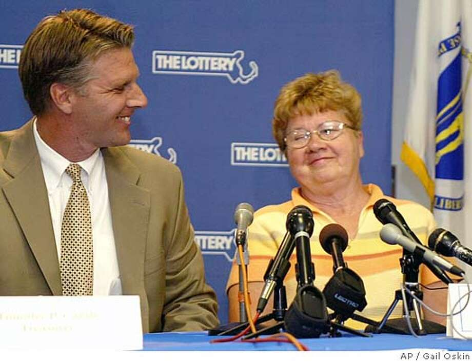 Geraldine Williams, right, smiles after being presented with a check for $294 million by Treasurer and Receiver General Timothy P. Cahill, left, at the Massachusetts State Lottery headquarters in Braintree, Mass., Friday, July 9, 2004. Williams, who was introduced at the news conference at state lottery headquarters Friday, said she's still stunned by her luck, a week after the numbers were drawn. (AP Photo/Gail Oskin) Photo: GAIL OSKIN