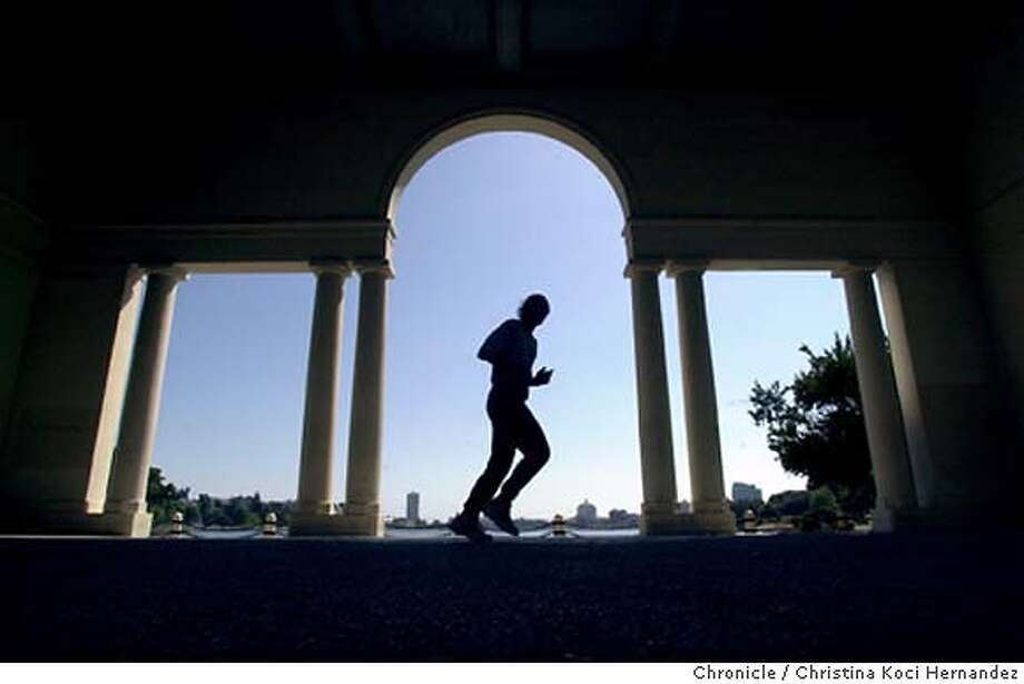 070604_weather_kocihernandez CHRISTINA KOCI HERNANDEZ/CHRONICLE  A jogger runs by the arches at Lake Merritt. People enjoy pleasant weather around Lake Merritt, in Oakland. MANDATORY CREDIT FOR PHOTOG AND SF CHRONICLE/ -MAGS OUT Photo: CHRISTINA KOCI HERNANDEZ