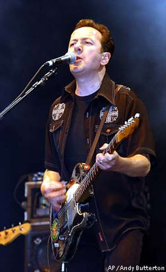 ** FILE ** File photo dated June 8, 2002, of Joe Strummer, frontman of the British punk band The Clash, who has died at the age of 50, his official website said Monday, Dec. 23, 2002. Strummer, born John Graham Mellor, helped make aggressive punk music a worldwide phenomenon with hits like 'Should I Stay or Should I Go' and 'London Calling'. (AP Photo/ PA, Andy Butterton/files) ** UNITED KINGDOM OUT MAGAZINES OUT ** Photo: YUI MOK