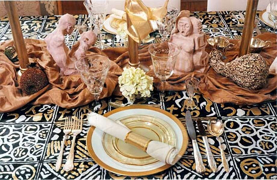 "Setting the mood: Sculptures, gourds and a copper-colored cloth enhance this Christmas table's African style. Photo from ""African-American Holiday Traditions''"