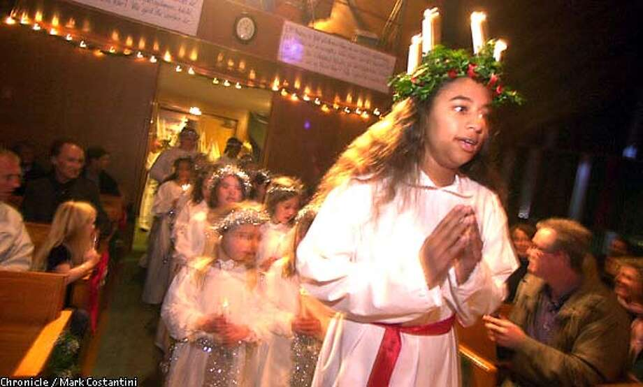 "Tilda Boyd, 13, her hair adorned with candles, leads a procession of children entering St. Luke's Lutheran Church in Walnut Creek at the beginning of a Mass celebrating Santa Lucia, the ""Queen of Light."" Chronicle photo by Mark Costantini"