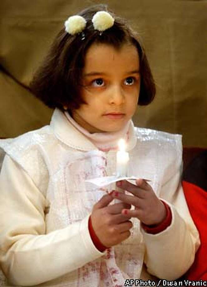 A girl holds a candle during a Christmas Eve Mass in St. Rafael's Church in Baghdad Tuesday, Dec. 24, 2002. Three percent of the population, or about one million peole, are Christian in Iraq. (AP Photo/Dusan Vranic) Photo: DUSAN VRANIC