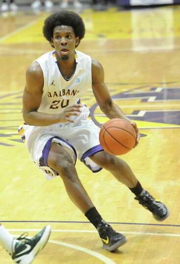 Gerardo Suero of UAlbany dribbles the ball during a basketball game against Binghamton at the SEFCU