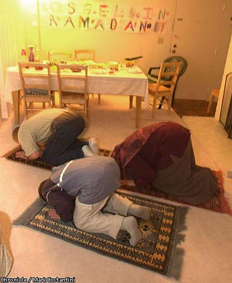 The Yesilyurt family of Cupertino prays at home after the breaking of the fast of Ramadan, a time of reflection, prayer and sacrifice. Chronicle photo by Mark Costantini
