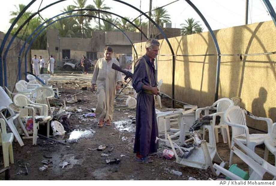 An Iraqi security officer stands at the scene of a car bomb that exploded Tuesday, July 6, 2004 in Khalis, Iraq northeast of Baghdad, killing 13 people who were attending a wake for the victims of a previous attack. (AP Photo/Khalid Mohammed) Photo: KHALID MOHAMMED