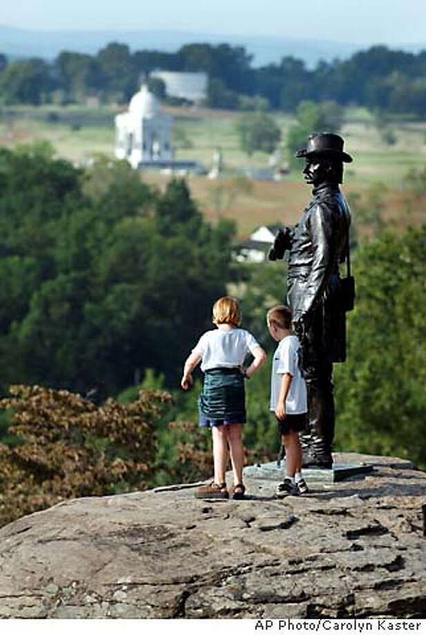 """TRAVEL GETTYSBURG, Penn. -- Shyann, 9, left, and her little brother Tyler Webber, 8, look out over the Gettysburg Battlefield as they stand next to the bronze statue """"The Eye of General Warren"""" on Little Round Top at Gettysburg National Military Park in Gettysburg, Pa., Sept. 7, 2003. (AP Photo/Carolyn Kaster) Photo: CAROLYN KASTER"""
