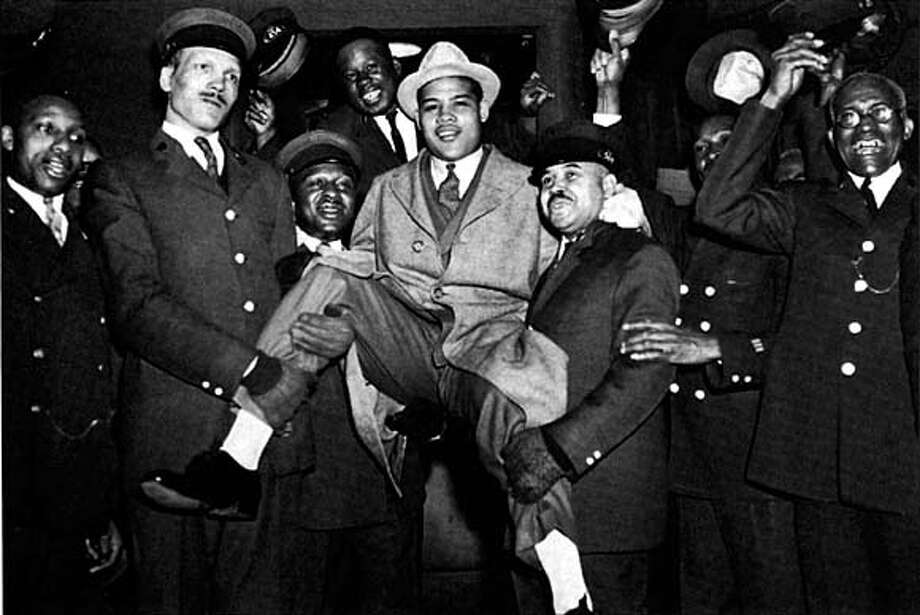 Porters and luggage-toting redcaps at New York's Grand Central Station show their affection for Joe Lewis as he arrives from Detroit for a 1941 bout against Billy Conn.