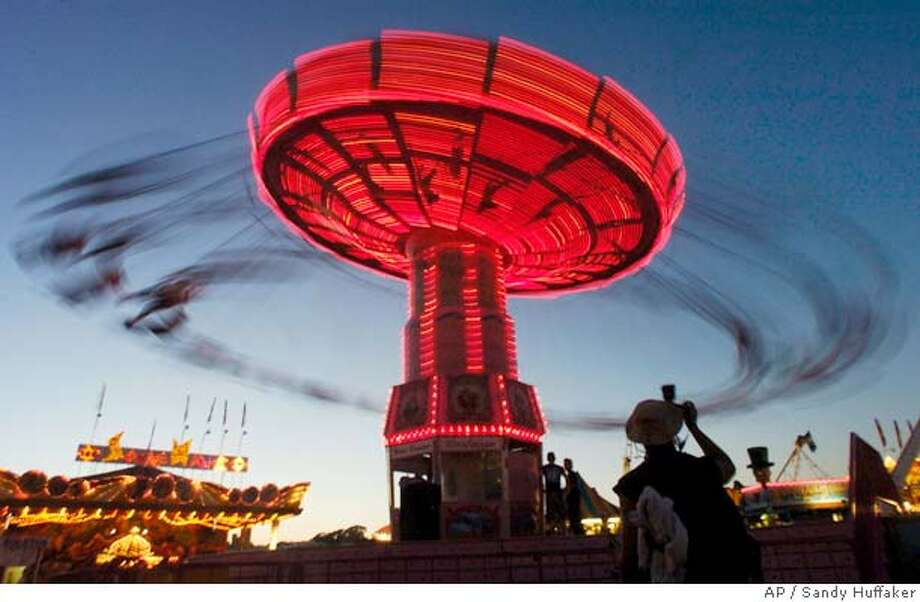 Fair-goers enjoy the rides on a summer evening at the San Diego County Fair in Del Mar, CA on Thursday, July 1, 2004. The Fair, which runs through July 5th, features games, rides exhibits and a large fireworks show on July 4th .(AP Photo/Sandy Huffaker) Photo: Sandy Huffaker