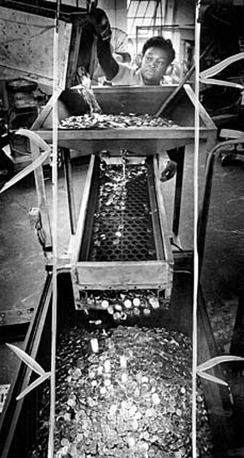 Employee Geraldine Richardson pours Susan B. Anthony coins into stamping machine at U.S. Mint in San Francisco in June 1979.