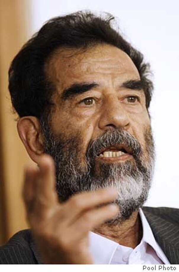 """Iraq's deposed dictator Saddam Hussein appears before an Iraqi tribunal July 1, 2004. Saddam refused to recognize its authority and said the """"real criminal"""" was U.S. President George W. Bush. Saddam, who arrived at the courthouse in handcuffs and chains, was read seven charges under a preliminary arrest warrant and told his rights, pool reporters granted access to the heavily guarded proceedings said. REUTERS/Handout Photo: HO"""
