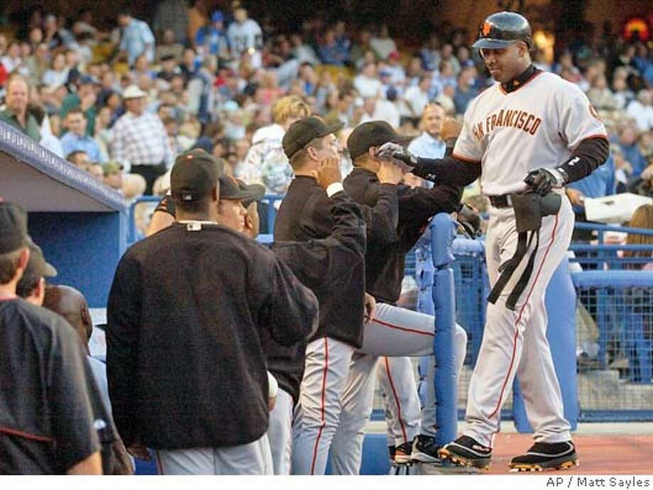 San Francisco Giants' Barry Bonds is congratulated by teammates after hitting a three run home run off of Los Angeles Dodgers pitcher Hideo Nomo in the third inning at Dodger Stadium in Los Angeles on Wednesday, June 30, 2004. (AP Photo/Matt Sayles) Photo: MATT SAYLES