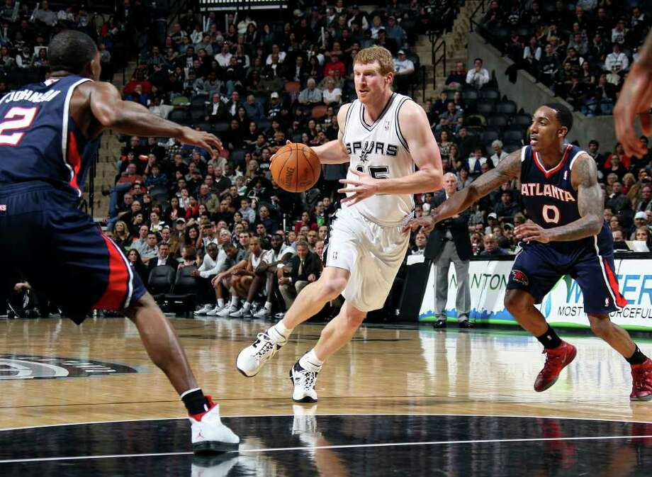Spurs Matt Bonner looks to pass the ball as he drives through Atlanta Hawks guards Joe Johnson, left, and Jeff Teague during the second half at the AT&T Center, Wednesday, Jan. 25, 2012. The Spurs won 105-83. Bonner tied with DeJuan Blair for 17 points and the team's high scorers. Teague had the game high of 20 points. Jerry Lara/San Antonio Express-News Photo: Jerry Lara, Express-News / © San Antonio Express-News