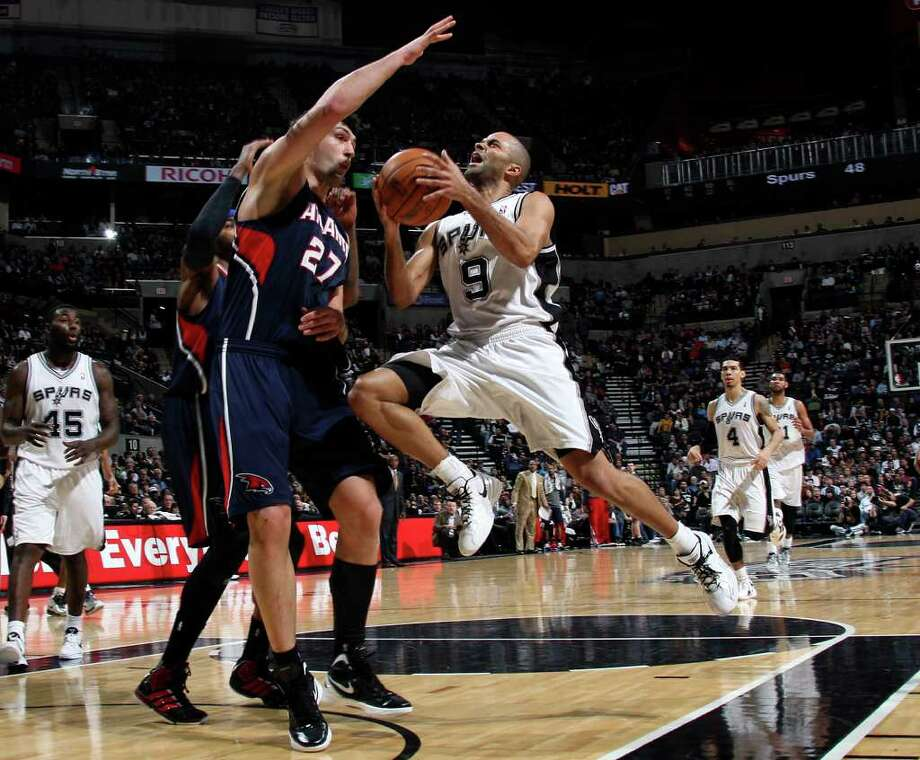 Spurs guard Tony Parker drives to the basket as Atlanta Hawks center Zaza Pachulia defends during the first half at the AT&T Center, Wednesday, Jan. 25, 2012. Jerry Lara/San Antonio Express-News Photo: Jerry Lara, Express-News / © San Antonio Express-News