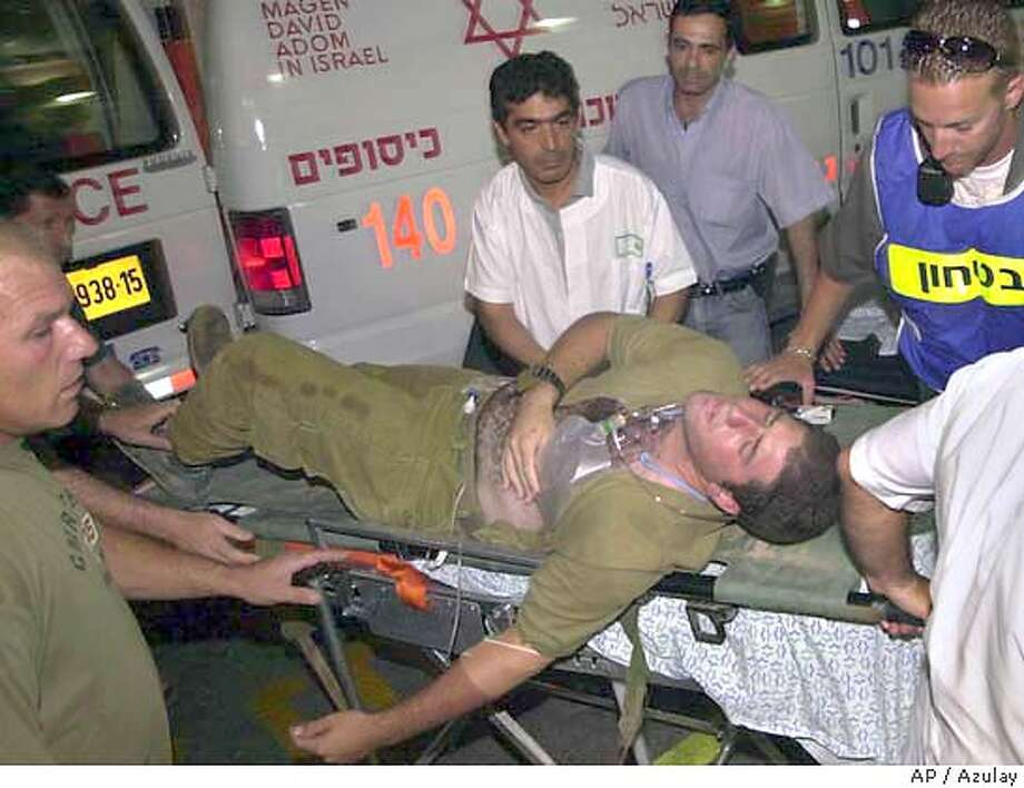 An Israeli soldier is wheeled into the hospital of the southern Israeli town of Beersheva late Sunday June 27, 2004. He was wounded during an attack by Palestinian militants that dug a tunnel under an Israeli army outpost in the heart of Gaza and exploded a bomb, collapsing a concrete building and wounding about 10 Israelis. The army declined comment on reports that several soldiers were killed in the attack, for which Hamas and the Al Aqsa Martyrs' Brigades claimed responsibility. (AP Photo/Azulay) ** ISRAEL OUT ** ISRAEL OUT Photo: AZULAY