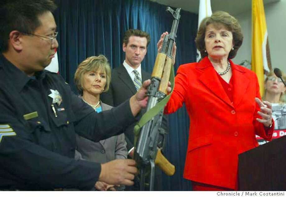 Sgt Rod Nakanishi with teh SFPD holds an AK-47 as (Barbara Boxer, Mayor Gavin Newsom, and Dianne Feinstein urge a renewal of the assault weapons ban as we approach the 11th anniversary of the shooting at 101 California.  Deanne FitzmauriceThe Chronicle Photo: Deanne Fitzmaurice