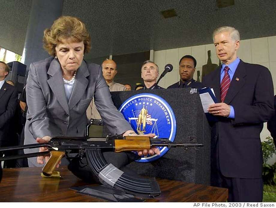 Sen. Dianne Feinstein, D-Calif., picks up an AK-47 at a speech about gun control with California Gov. Gray Davis, far right, Sheriff Lee Baca, back left, LAPD Chief William Bratton and Santa Monica Police Chief James T. Butts, second right, at a news conference in Los Angeles, Thursday, Aug. 21, 2003. The group urged Congress to re-authorize the assault weapons ban. (AP Photo/Reed Saxon) CAT w/RECALL Photo: REED SAXON