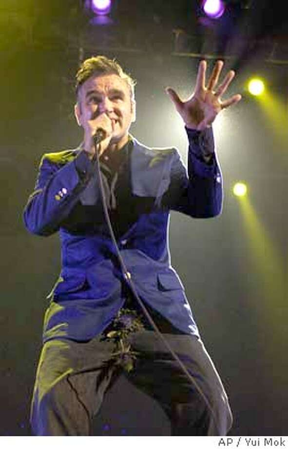 """Morrissey performs on stage during a concert to promote his new album, """"You Are The Quarry,"""" at the Manchester Evening News Arena in Manchester, England, Saturday, May 22, 2004. (AP Photo/PA, Yui Mok )**UK OUT: MAGS OUT: ** UK OUT, ,MAGS OUT/A MAY 22 2004 PHOTO Photo: YUI MOK"""