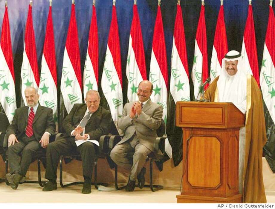 Iraqi President Ghazi Al-Yawer, far right, delivers a speech as members of the government applaud in front of a row of Saddam Hussein-era Iraq national flags at a swearing in ceremony in Baghdad, Iraq, Monday June 28, 2004. From left are Vice President of Iraq Ibrahim Al-Jaafari , Prime Minister Iyad Allawi, and Deputy Prime Minister Barham Salih. (AP Photo/David Guttenfelder) Photo: DAVID GUTTENFELDER