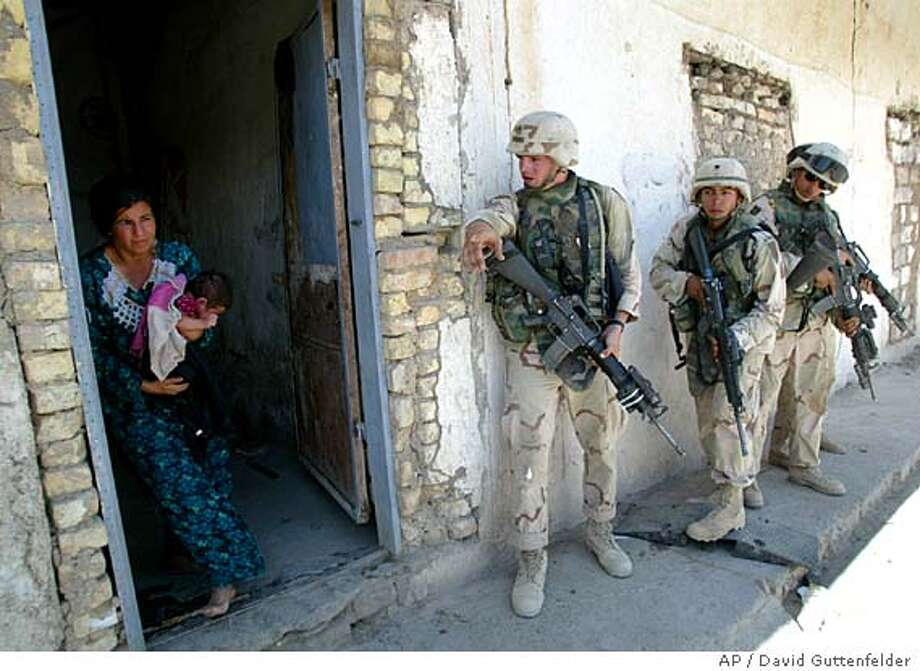 U.S. soldiers from the First Infantry Division ask an Iraqi woman to leave her home briefly as they make house to house searches looking fo weapons after a tip from a local informant in Baqouba, Iraq, Saturday, June 26, 2004. (AP Photo/David Guttenfelder) Photo: DAVID GUTTENFELDER