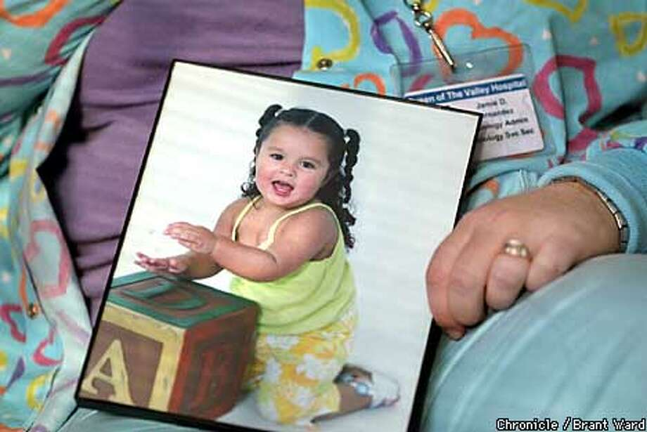 Jamie Hernandez holds a portrait of her daughter Julian, 2 and a half years, whom she has to place in daycare endlessly in order to do her hospital job. By Brant Ward/Chronicle Photo: BRANT WARD