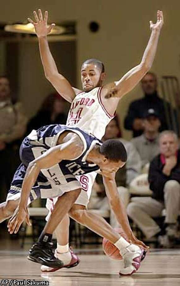 Rice guard Omar-Seli Mance is closely covered by Stanford guard Julius Barnes in the first half, Sunday, Nov. 24, 2002, in Stanford, Calif. Barnes was high scorer with 28 points and tied a school record with eight 3-point baskets. Stanford defeated Rice 79-62. (AP Photo/Paul Sakuma) Photo: PAUL SAKUMA